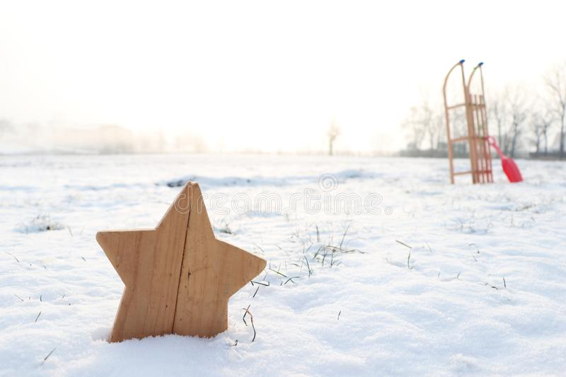 Деревянная звезда и сани в ландшафте сцены снега зимы стоковое изображение