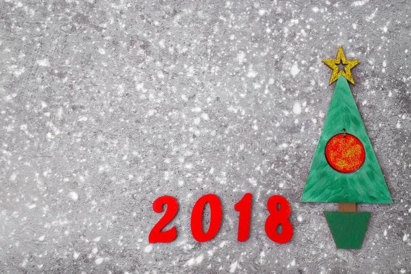 Деревянная зеленая рождественская елка, подписывает 2018 от деревянных красных писем, серая конкретная предпосылка Счастливый фон стоковое изображение rf