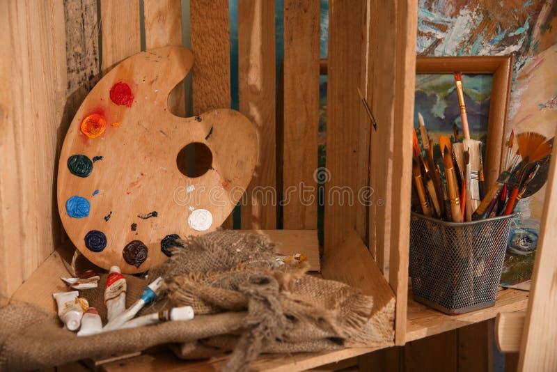 Деревянная клеть с красками и инструментами в мастерской художника стоковая фотография