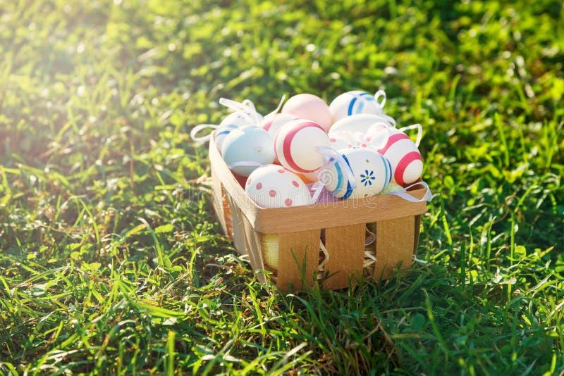 Деревянная корзина с лож апельсина, желтых и зеленых яя на траве весны зеленой на солнечном свете Счастливая пасха! Украшение, ох стоковая фотография
