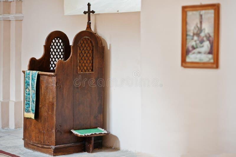 Деревянная коричневая исповедническая коробка с крестом на церков стоковые изображения