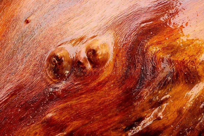 Деревянная коричневая красная картина текстуры предпосылки Влажная абстрактная деревянная поверхность с светлыми отражениями стоковое фото