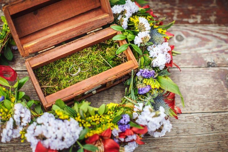 Деревянная коробка с обручальными кольцами в цветках стоковое фото