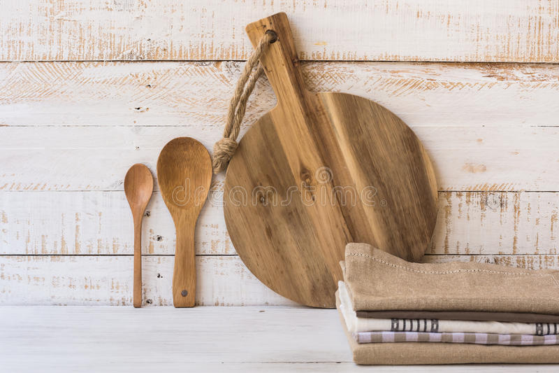Деревянная круглая разделочная доска, ложки, стог linen полотенец кухни на белой предпосылке древесины планки стоковая фотография