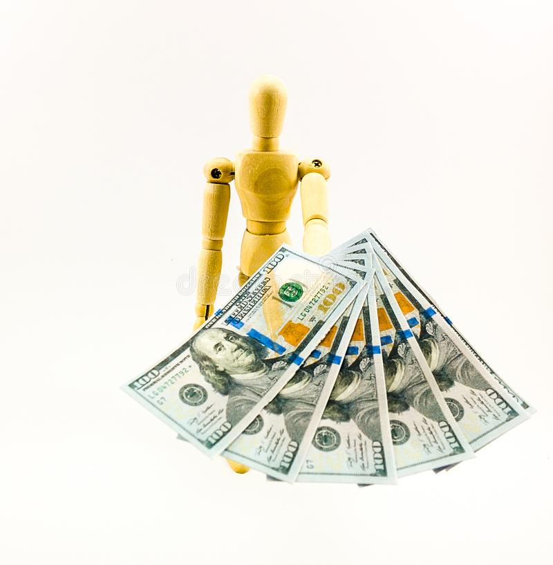 Деревянная кукла вручая 100 USD счетов стоковое фото rf