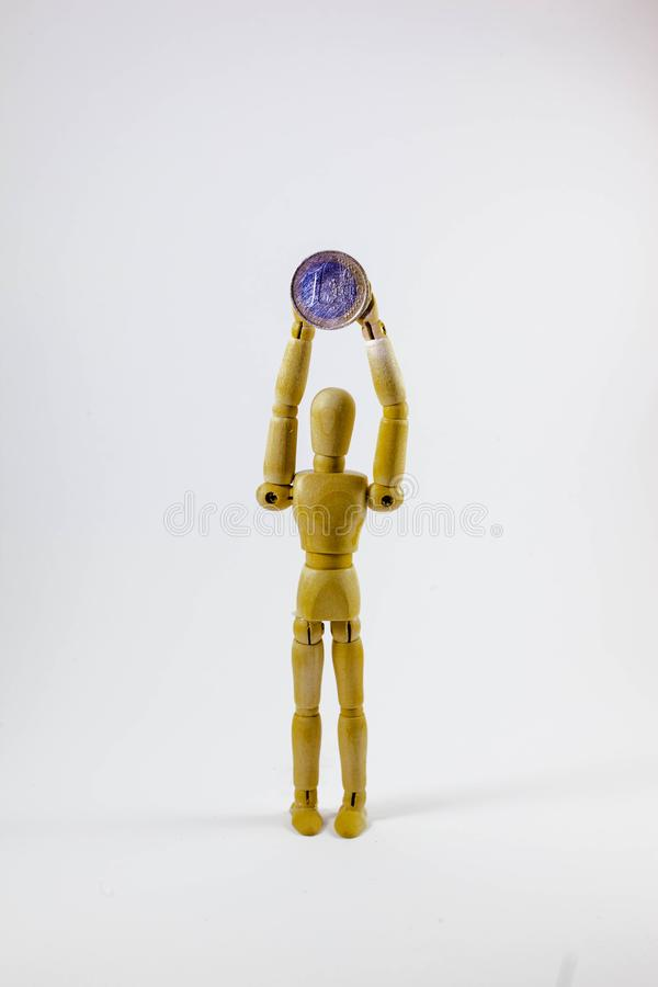 Деревянная кукла держа монетки евро стоковая фотография