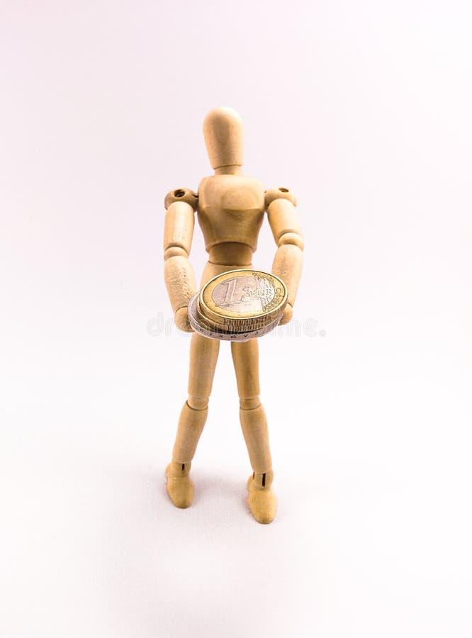 Деревянная кукла держа монетку евро стоковое изображение