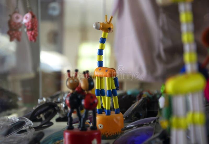 Деревянная кукла жирафа украшенная в стеклянном шкафе показывая шлихту ювелирных изделий стоковые фото