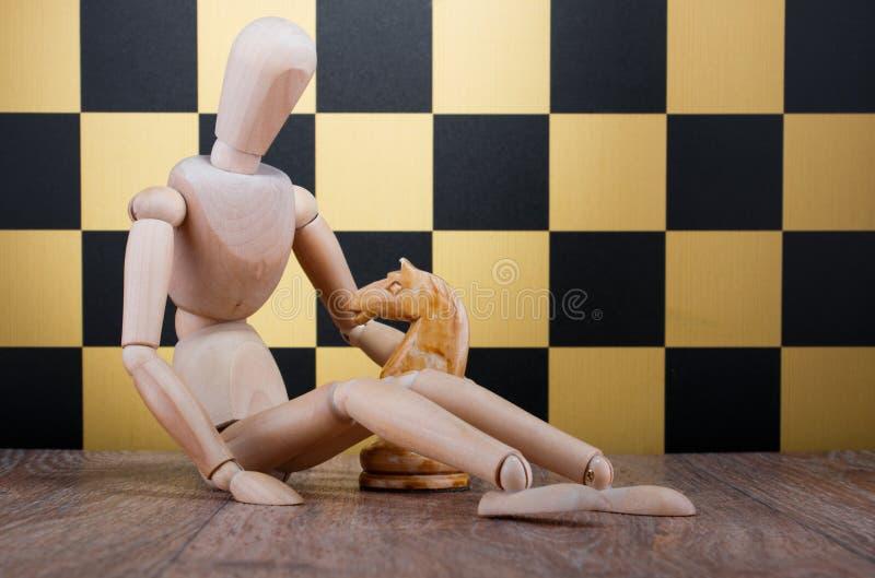 Деревянная кукла с рыцарем шахмат на предпосылке доски стоковые изображения rf