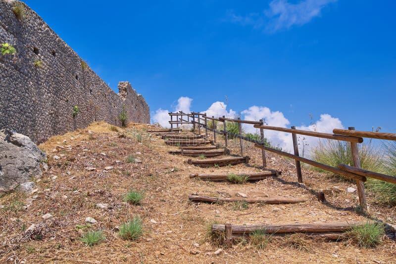 Деревянная лестница рядом с каменной крепостной стеной стоковые изображения rf