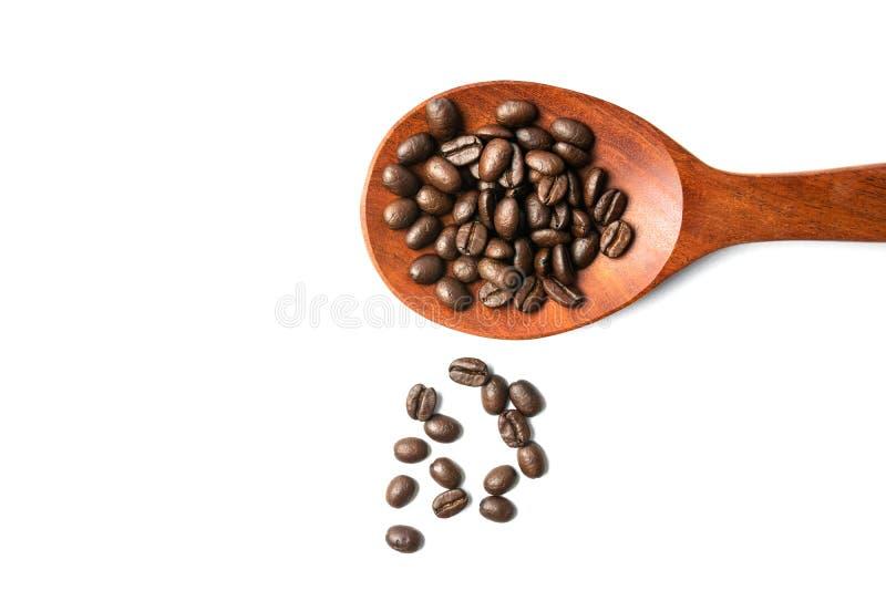 Деревянная ложка с распространенными кофейными зернами изолированными на белом космосе предпосылки и экземпляра стоковое изображение