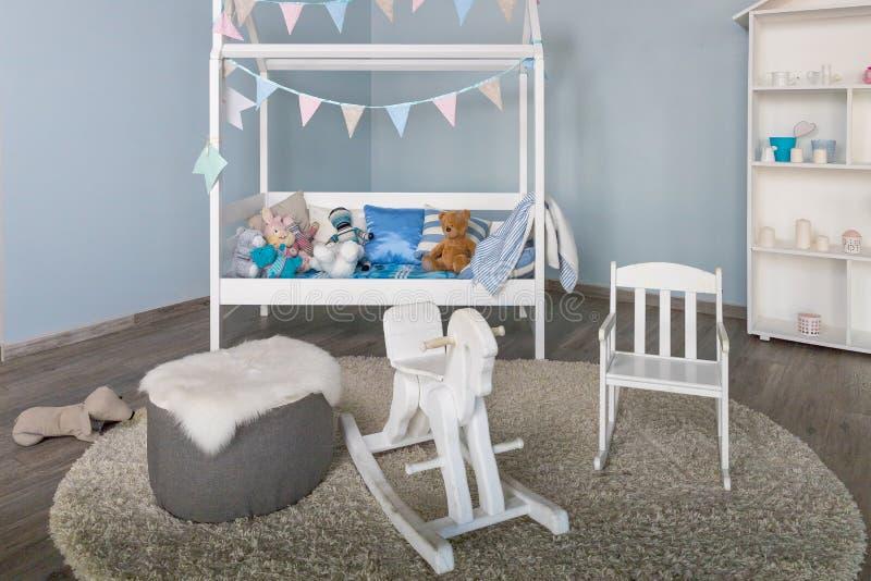 Деревянная лошадь в интерьере комнаты мальчика детей Стильная мебель в комнате однокрасочного просторного ребенк Современный стил стоковые фото