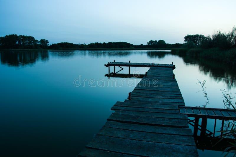 Деревянная мола над спокойным мистическим озером стоковые фото