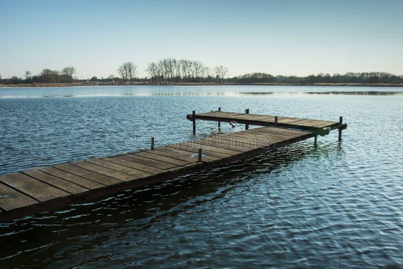 Деревянная мола на озере Деревья на горизонте и ясном небе стоковая фотография