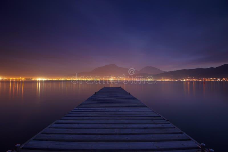 Деревянная мола на отражении захода солнца и неба моря мочит выдержка длиной стоковое изображение rf