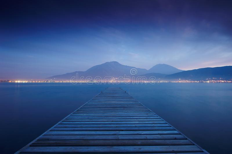 Деревянная мола на отражении захода солнца и неба моря мочит выдержка длиной стоковые фото