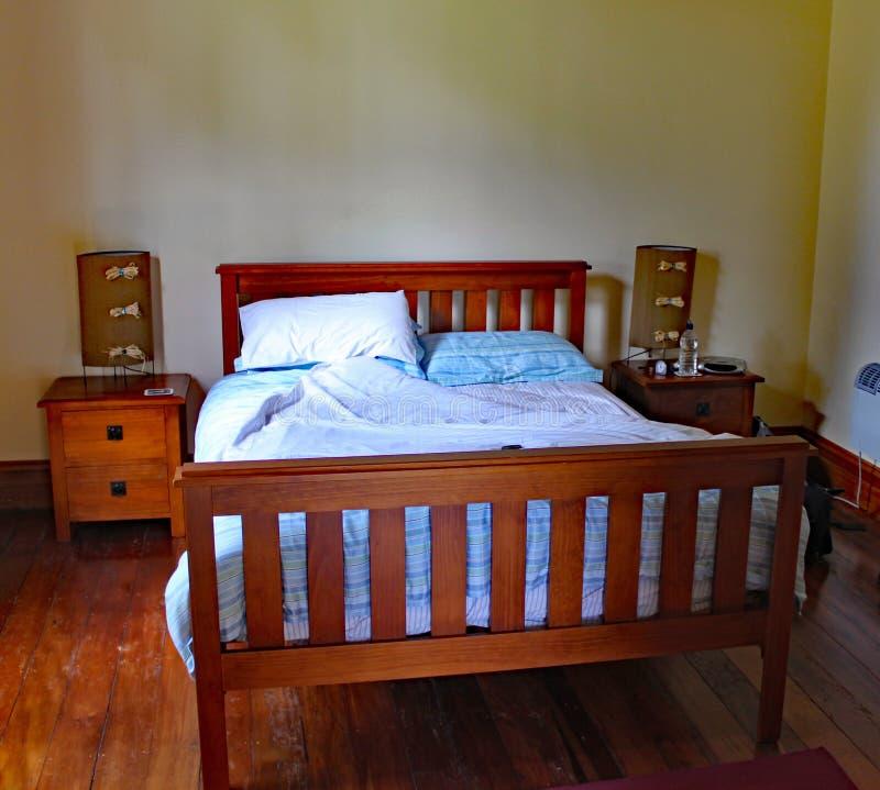 Деревянная обрамленная двуспальная кровать в своеобразной арендуемой собственности в Masterton в Новой Зеландии стоковое изображение
