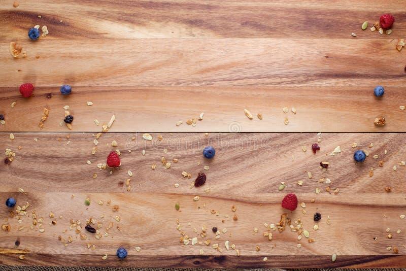 Деревянная доска при ягоды и Granola разбросанные с космосом текста стоковая фотография