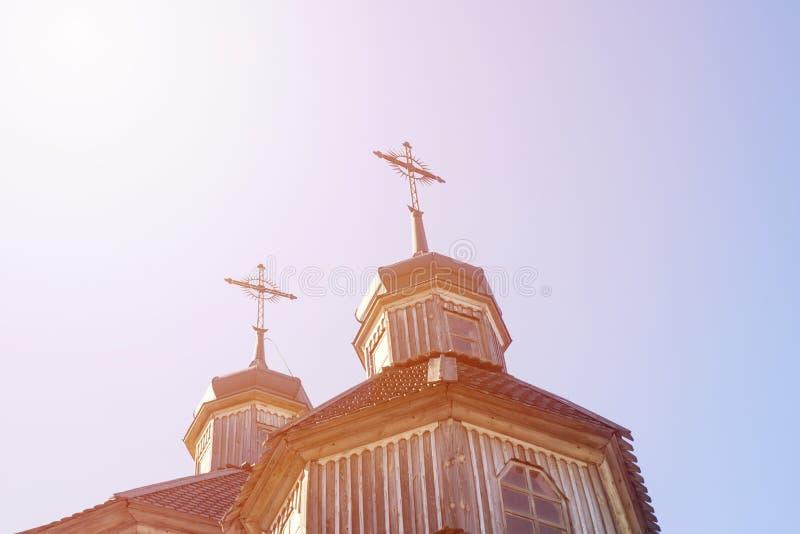 Деревянная перекрестная предпосылка Деревянный крест на простом steeple установил против голубого неба Крыша церков с крестом Цер стоковые фото