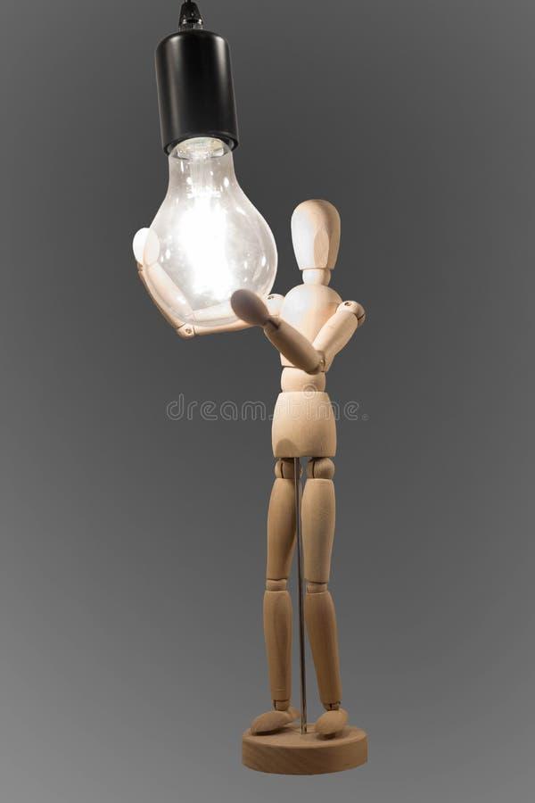 Деревянная персона держит горящую электрическую лампочку в руке стоковые изображения