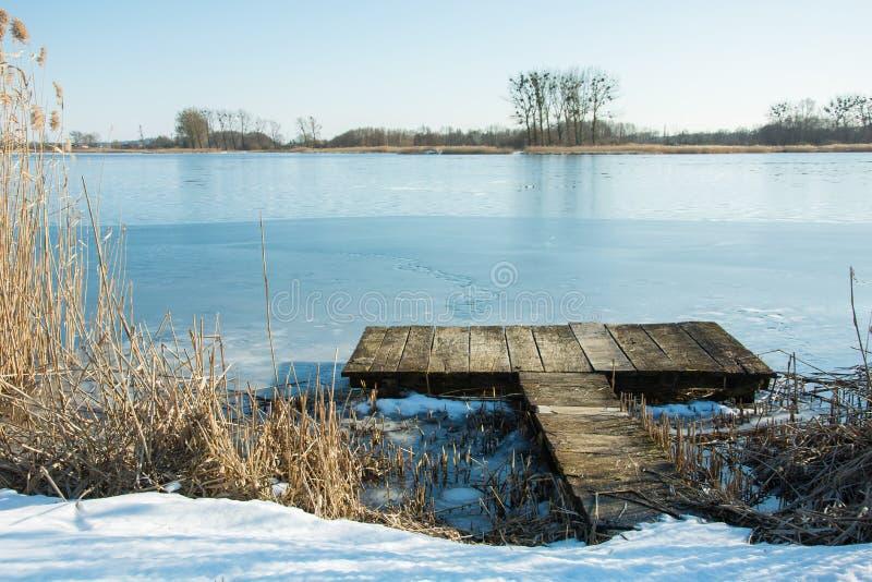 Деревянная платформа на замороженном озере и деревья на горизонте стоковая фотография