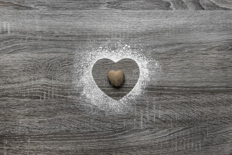 Деревянная предпосылка с напудренным снегом порошка силуэт сердца полита и лежит печенье в форме сердца стоковая фотография rf