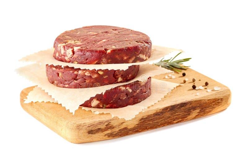 Деревянная прерывая доска с стогом сырцовых пирожков бургера говядины на белизне стоковая фотография