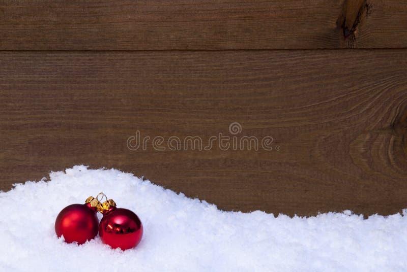 Деревянная предпосылка рождества на снеге, красных шариках как украшение стоковое фото rf