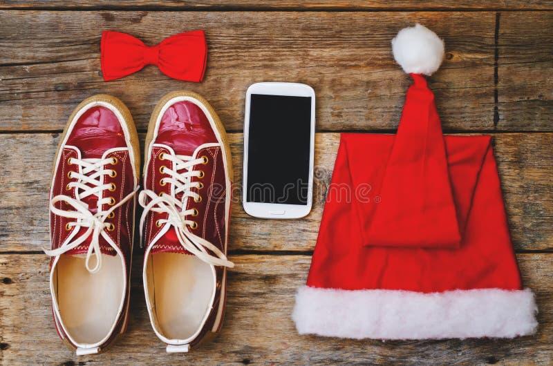 Деревянная предпосылка с клобуком тапок телефона красным и смычком стоковая фотография