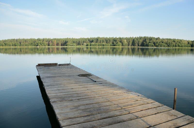 Деревянная пристань на озере в после полудня в windless погоде стоковые фотографии rf