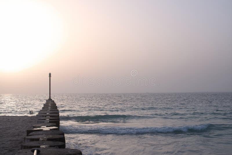 Деревянная пристань со штендерами на пляже сумерек лета стоковое фото rf