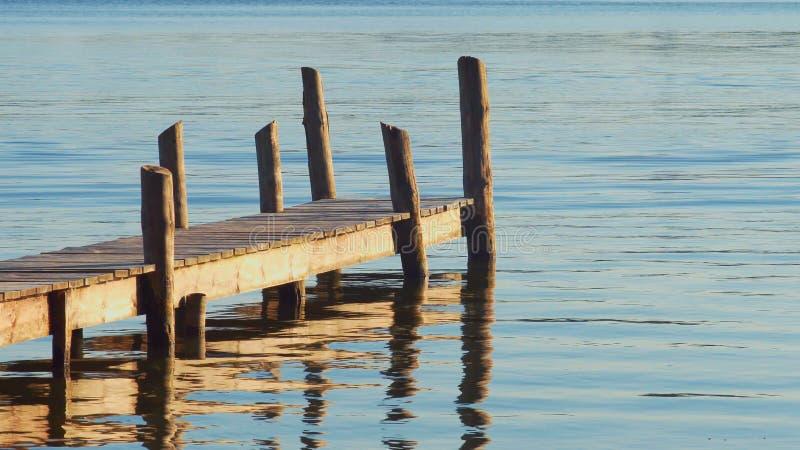 Деревянная пристань шлюпки на тихом озере на заходе солнца стоковое фото rf