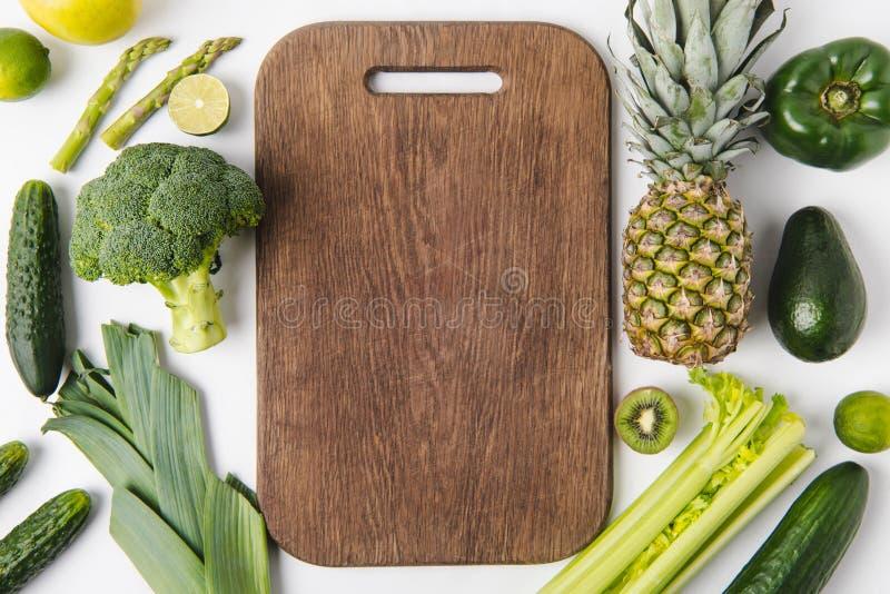Деревянная разделочная доска при зеленые овощи и плодоовощи изолированные на белой предпосылке стоковые изображения