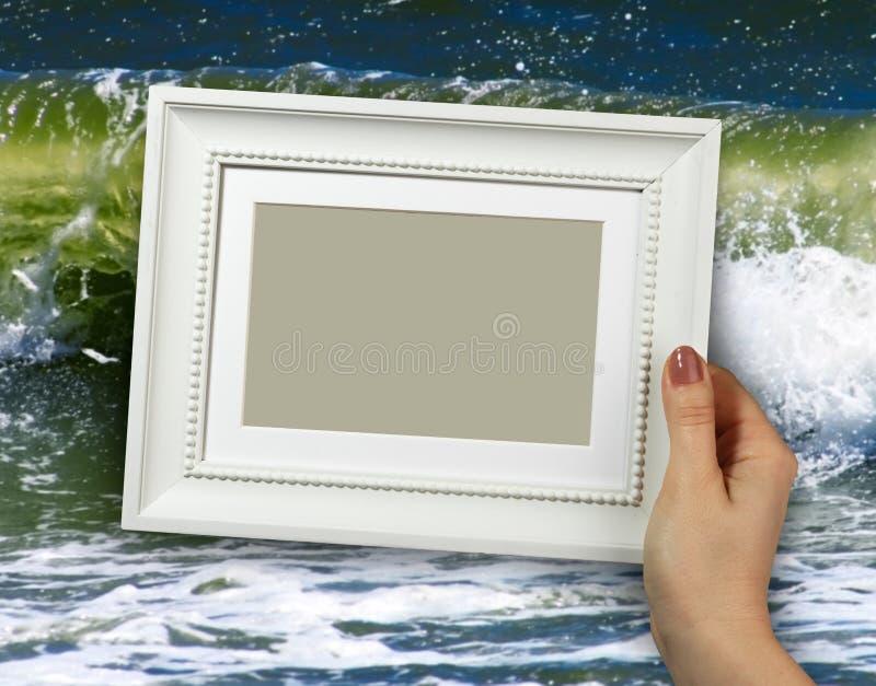 Деревянная рамка в руках женщины на море предпосылки развевает на пляжах стоковое изображение rf