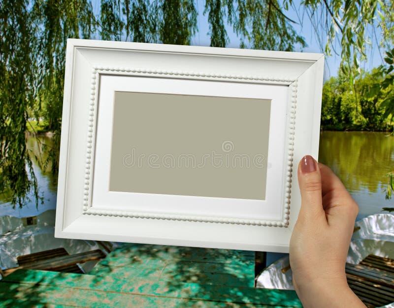 Деревянная рамка в руках женщины Шлюпка на озере на предпосылке стоковая фотография