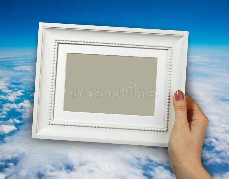 Деревянная рамка в руке женщины на предпосылке неба стоковая фотография