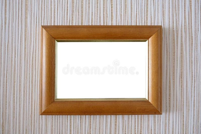 Деревянная рамка на стене с белой предпосылкой в середине стоковые изображения rf