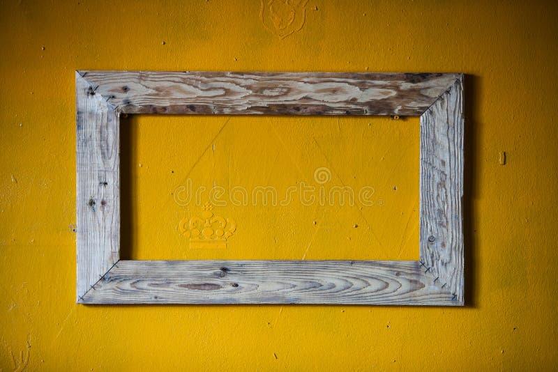 Деревянная рамка с желтой предпосылкой стоковые изображения rf