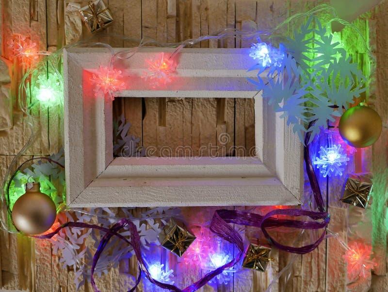 Деревянная рамка с пустым космосом на каменной текстурной предпосылке украшена с праздничным освещением и украшением рождества стоковые изображения rf