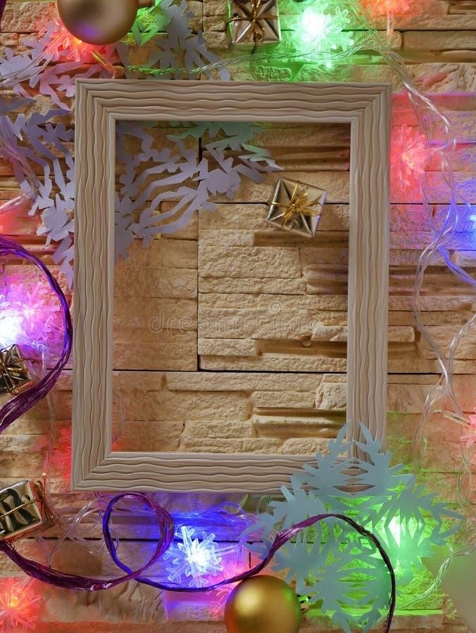 Деревянная рамка с пустым космосом на каменной текстурной предпосылке украшена с праздничным освещением и украшением рождества стоковое фото