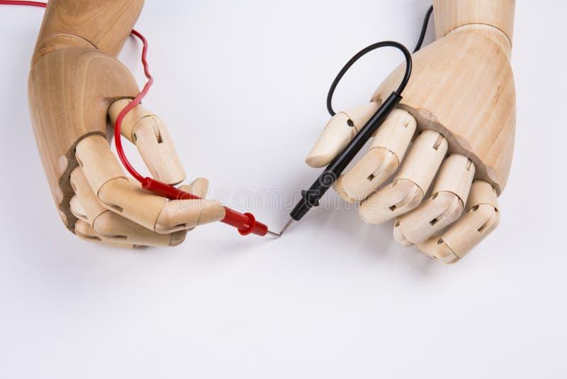 Деревянная рука и электрический вольтамперомметр стоковые фото