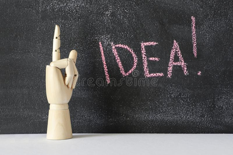 Деревянная рука указывая вверх по указательному пальцу Побеленное мелом слово ИДЕЯ стоковая фотография