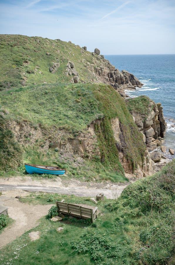 Деревянная скамья и маленькая лодка на побережье Англии Корнуолла стоковые изображения rf