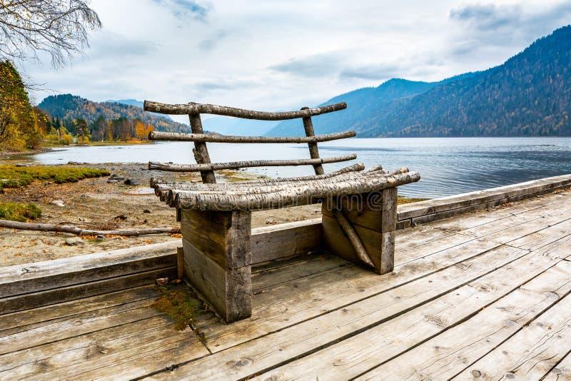Деревянная скамья на береге озера горы стоковая фотография rf