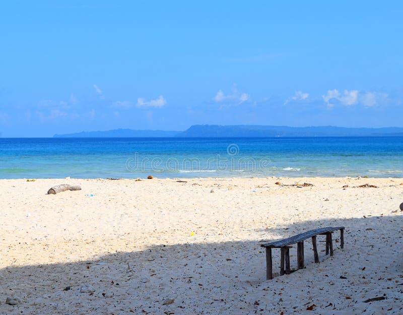 Деревянная скамья под тенью на мирном уединенном песчаном пляже, голубом океане и небе - Laxmanpur, острове Нейл, Andaman, Индии стоковые фотографии rf