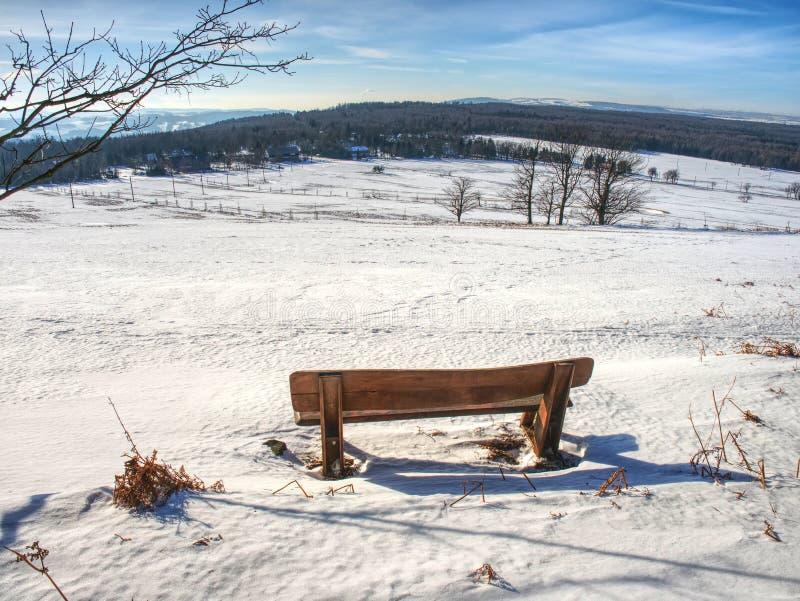 Деревянная скамья предусматриванная в снеге стоковые изображения rf
