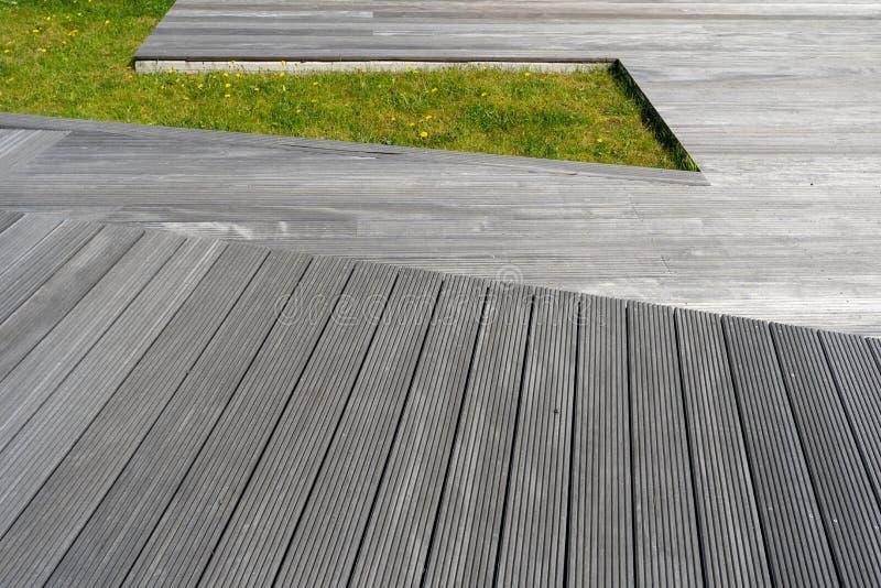 Деревянная скамья улицы во дворе города с зеленой лужайкой стоковые фотографии rf