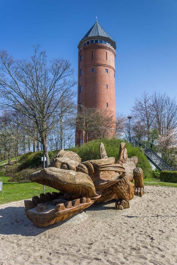 Деревянная скульптура дракона перед водонапорной башней в Grimmen стоковая фотография rf