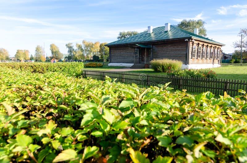 Деревянная старая коричневая школа в деревне Konstantinovo с зеленым цветом на переднем плане от XVIII века Место где известный п стоковое изображение rf