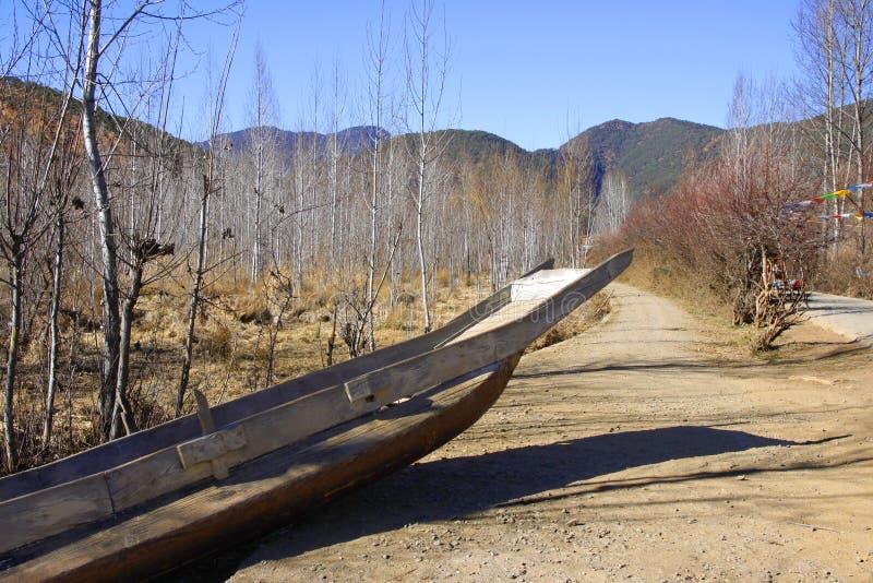 Деревянная старая рыбацкая лодка в лесе в пятне озера Lugu сценарном и высоком небе стоковая фотография